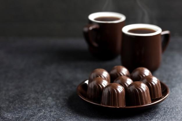 Caramelle di cioccolato su un piatto e due tazze di caffè caldo sulla superficie nera con lo spazio della copia