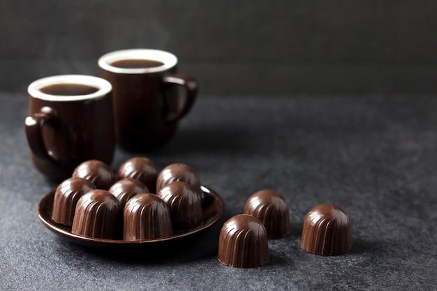 Caramelle di cioccolato su un piatto e due tazze di caffè caldo sul nero