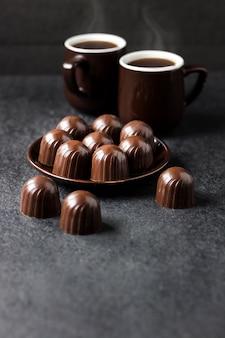 Caramelle di cioccolato su un piatto e due tazze di caffè caldo su sfondo scuro