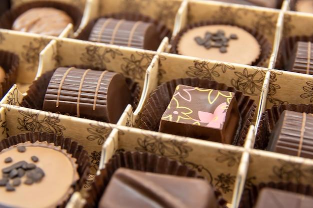 Caramelle al cioccolato in una scatola aperta primo piano di caramelle al cioccolato dolci al cioccolato assortiti