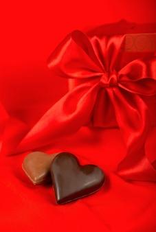 Caramelle al cioccolato a forma di cuore su fondo rosso