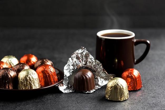 Caramelle al cioccolato avvolte in un foglio multicolore e due tazze di caffè