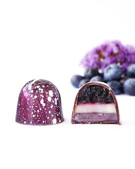 Caramella di cioccolato in un taglio su uno sfondo bianco mirtillo e lavanda