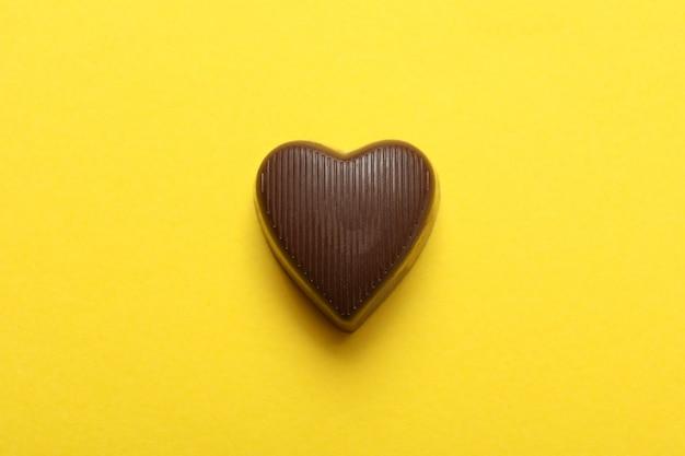 Caramella di cioccolato a forma di cuore su sfondo giallo