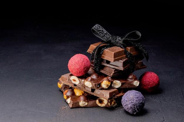 Cioccolatini al tartufo con pezzi di cioccolato e cacao in polvere volante su fondente.