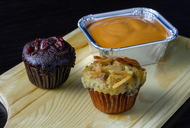 Muffin al cioccolato e ciliegie, cupcake alla banana con topping di mandorle e torta al cioccolato fondente con tè al latte in vassoio di alluminio su tavola di legno