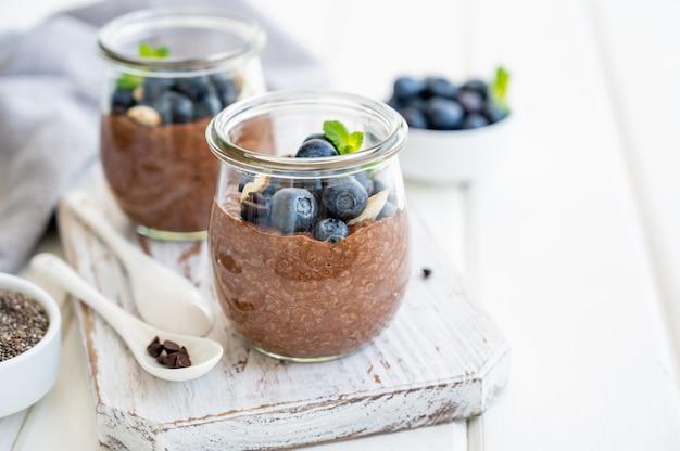 Budino di chia al cioccolato con mirtilli, mandorle e menta sopra in un barattolo di vetro