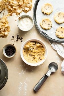 Processo di cottura dei biscotti con gocce di cioccolato. biscotti fatti in casa, vista dall'alto.