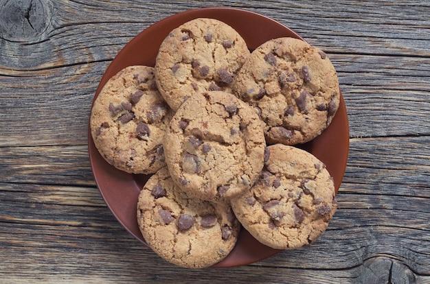 Biscotti di pepita di cioccolato su una zolla marrone sulla vecchia tavola di legno