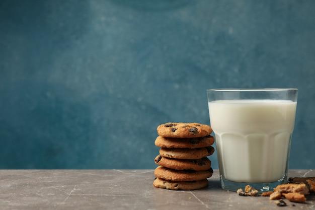 Biscotti al cioccolato e bicchiere di latte sul tavolo marrone