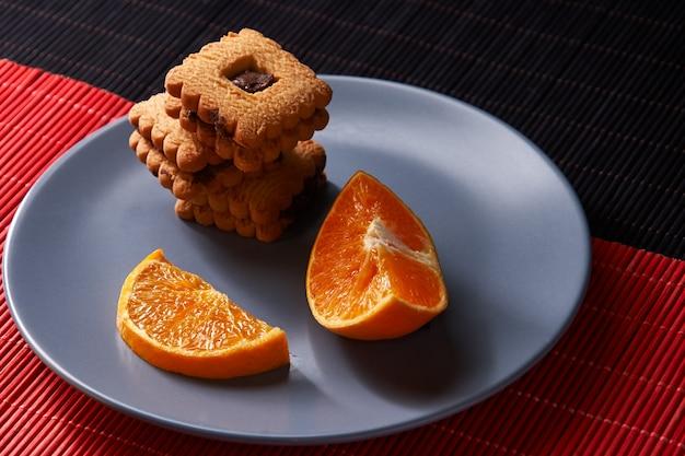 Biscotti di pepita di cioccolato e pezzo di arancia sul piatto e sulla superficie rossa e nera con il posto per il fuoco selettivo del testo con copyspace