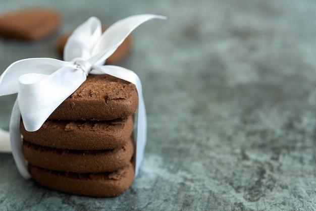Biscotti al cioccolato legati con un nastro bianco su sfondo scuro on