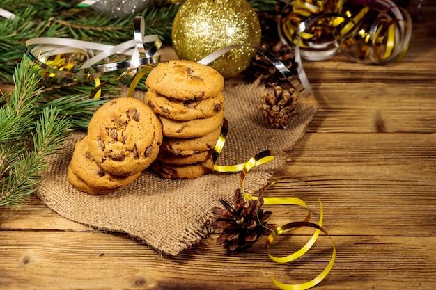 Biscotti al cioccolato con decorazioni natalizie su tavola di legno