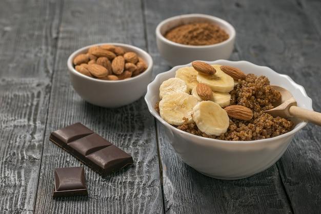 Scaglie di cioccolato e porridge di quinoa con banana e mandorle su un tavolo rustico. dieta sana.