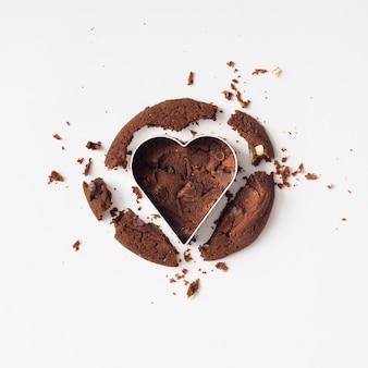 Biscotto al cioccolato tagliato con taglierina a cuore. lay piatto. concetto di amore.