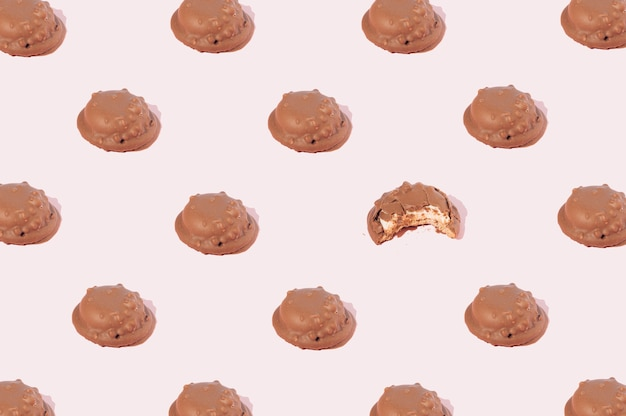 Biscotti al cioccolato disposti secondo uno schema in cui un biscotto viene morso su uno sfondo rosa. concetto di cibo dolce per feste.