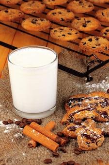 Biscotti al cioccolato sulla cottura con un bicchiere di latte da vicino