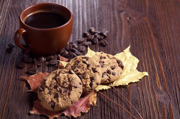 Biscotti al cioccolato e tazza di caffè caldo sul tavolo di legno marrone