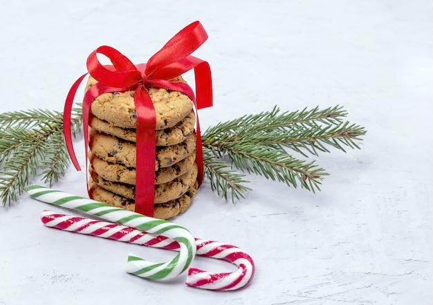 Biscotti al cioccolato legati con un nastro rosso lecca lecca e un ramo di abete