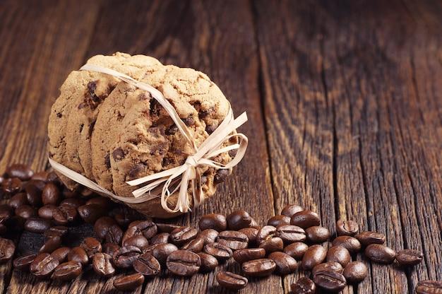 Biscotti al cioccolato legati con un nastro e chicchi di caffè su un tavolo di legno scuro