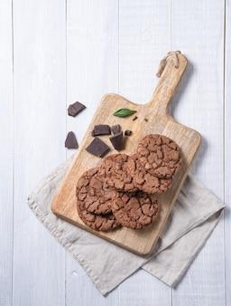 Un biscotti al cioccolato con gocce di cioccolato sul tagliere di legno con tovagliolo su un tavolo di legno bianco. vista dall'alto e copia spazio