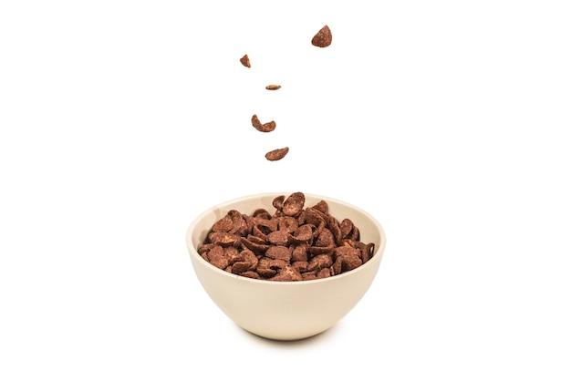 Fiocchi di mais al cioccolato che cadono nella ciotola bianca isolata su priorità bassa bianca.