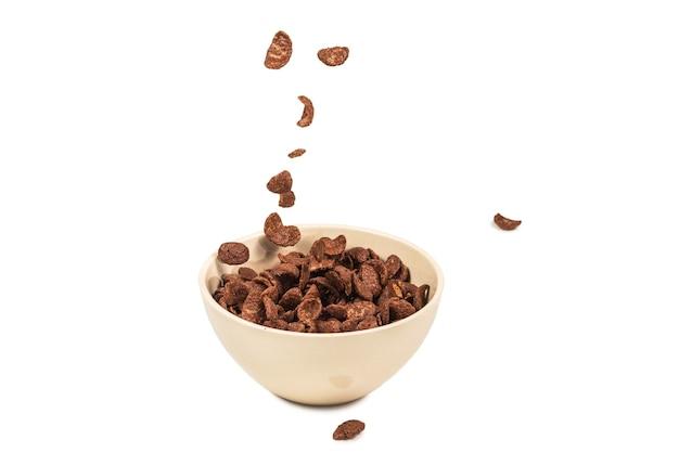 Fiocchi di mais al cioccolato che cadono nella ciotola bianca isolata su bianco. movimento. copyspace.
