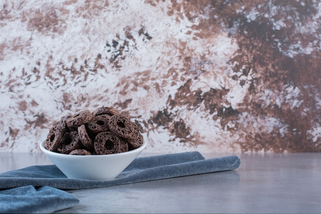 Anelli di mais al cioccolato isolati su piastra bianca su una superficie di pietra
