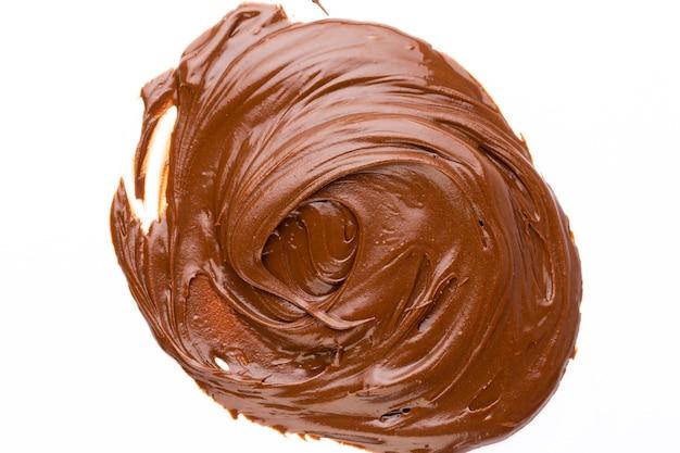 Crema al cioccolato isolata sulla superficie bianca. lay piatto.
