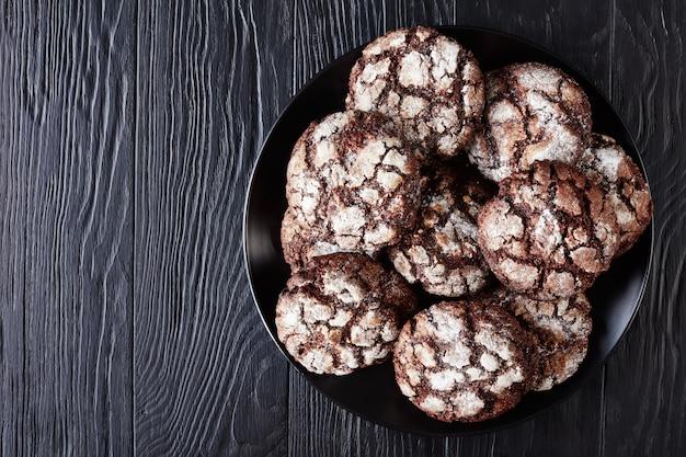 Biscotti crinkle al cioccolato. biscotti al cioccolato incrinati. biscotti al cioccolato, biscotti di natale su una piastra nera su un tavolo di legno, vista da sopra, flatlay, spazio copia, close-up