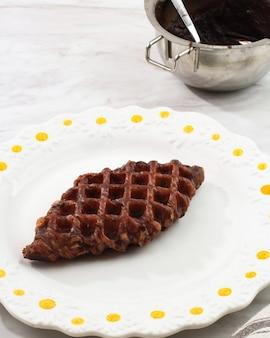 Croffle al cioccolato o cialda croissant in piastra bianca. croffle è una torta snack virale dalla corea del sud.