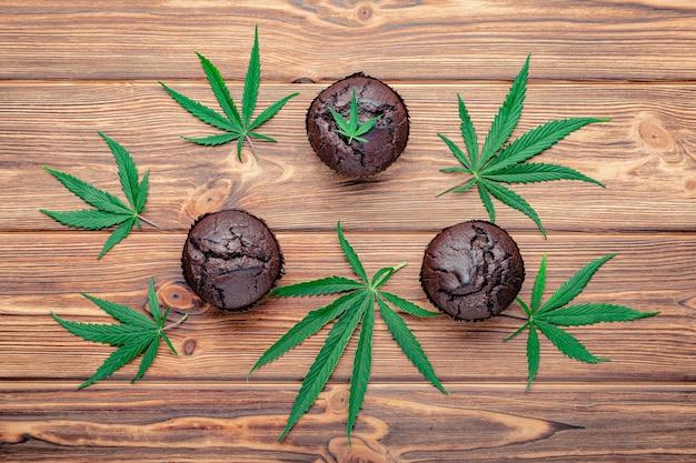 Muffin cupcake al cioccolato con foglie di cannabis, cbd alla cannabis. droghe di canapa di marijuana medica nel dessert alimentare. muffin alle erbette al cioccolato. cupcake con marijuana su tavola di legno marrone scuro laici piatta.