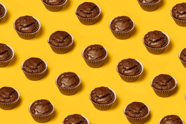 Modello di cupcakes o biscotti al cioccolato su uno sfondo giallo. minimalismo estivo. lay piatto isometrico. vista dall'alto. concetto di cibo.