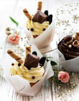 Cupcakes al cioccolato su fondo di legno bianco