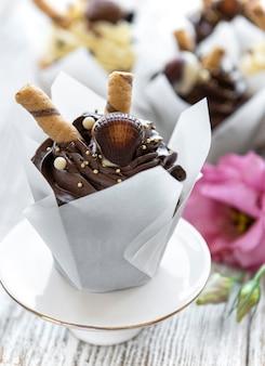 Cupcakes al cioccolato sulla tavola di legno bianca