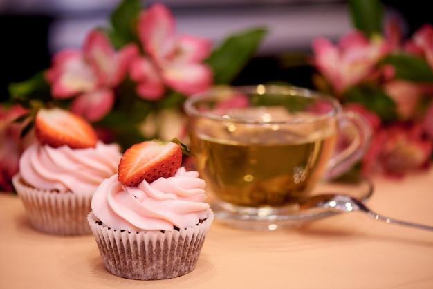 Cupcakes al cioccolato con fragole. cupcakes con una tazza di tè.