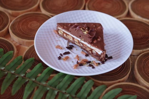 Dessert al cioccolato in un taglio con ripieno di noci caramellate e torroni la torta è ricoperta di cioccolato