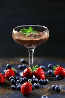 Dessert al cioccolato in vetro e frutti di bosco freschi sulla parete in legno di colore