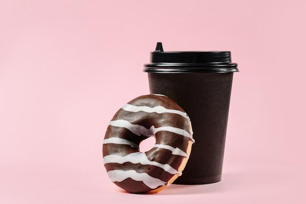 Ciambella al cioccolato e bicchiere di carta per caffè o tè