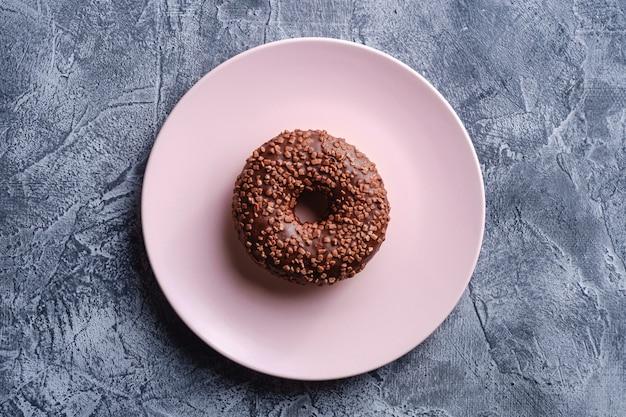 Ciambella al cioccolato con un pizzico sul piatto rosa, dolce cibo da dessert glassato su priorità bassa strutturata concreta, vista dall'alto
