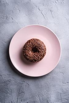 Ciambella al cioccolato con un pizzico sul piatto rosa, dolce cibo da dessert lustrato sulla tavola strutturata concreta, vista dall'alto