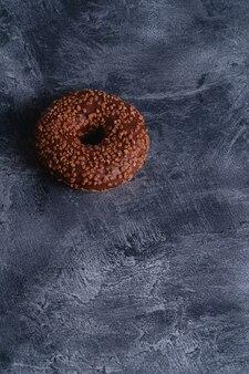 Ciambella al cioccolato con spruzza, cibo dolce da dessert glassato su cemento scuro strutturato, angolo vista copia spazio