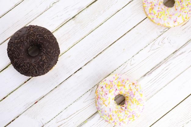 Ciambella al cioccolato su uno sfondo di legno bianco e una manciata di dolci ornamenti