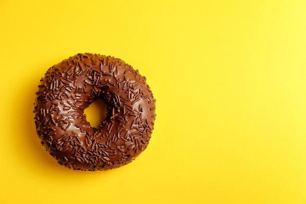 Ciambella al cioccolato su sfondo giallo vista dall'alto
