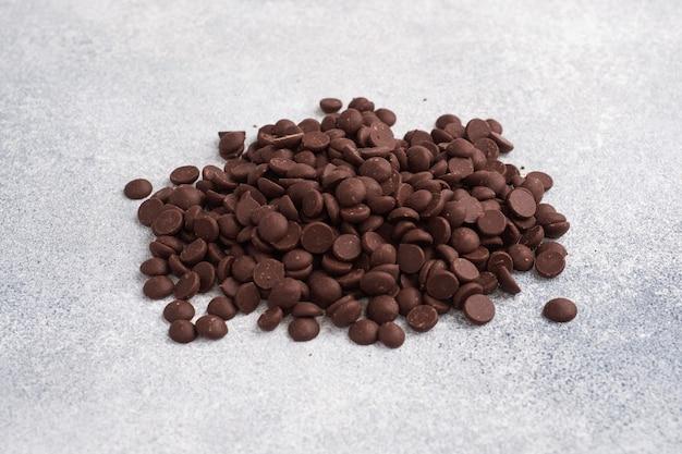 Gocce di cioccolato su un cemento grigio. pezzi di cioccolato per la decorazione di dessert.