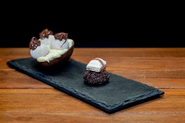 Uovo di pasqua al cioccolato e tartufo al cioccolato sopra la pietra nera con fondo in legno