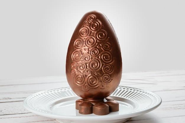 Uovo di pasqua di cioccolato decorato con vernice color rame commestibile. su una tavola di legno bianca.