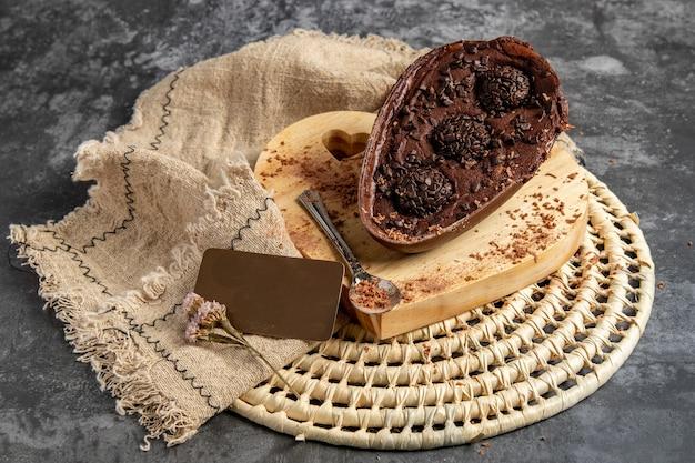 Uovo di pasqua di cioccolato ripieno di brigadeiro e accompagnato da elementi decorativi e su supporto in legno a forma di cuore e fondo grigio.