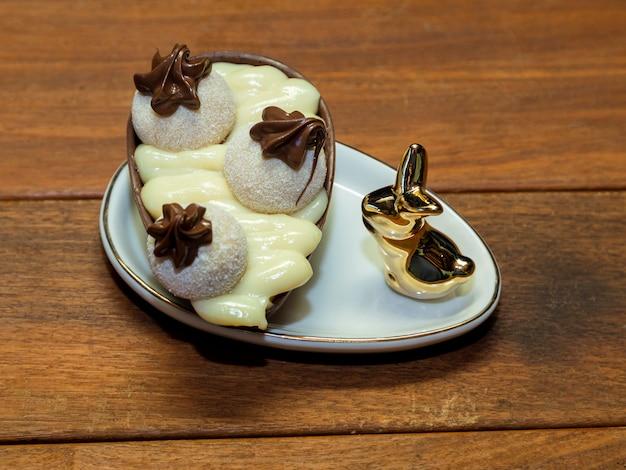 Uova di pasqua al cioccolato in ciotola con coniglio in porcellana