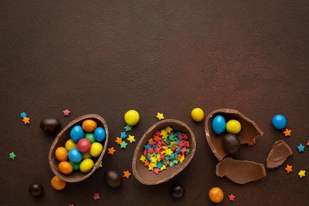 Uova di pasqua al cioccolato e dolci colorati su sfondo di pietra biglietto di auguri